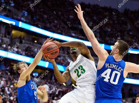 Oregon forward Elgin Cook, middle, shoots between Duke guard Luke Kennard, left, and center Marshall Plumlee during the first half of an NCAA college basketball game in the regional semifinals of the NCAA Tournament, in Anaheim, Calif