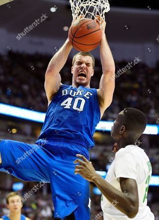 Duke center Marshall Plumlee, left, ducks over Oregon forward Chris Boucher during the second half of an NCAA college basketball game in the regional semifinals of the NCAA Tournament, in Anaheim, Calif