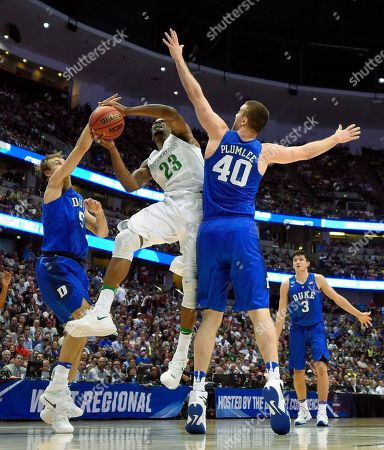Oregon forward Elgin Cook shoots between Duke guard Luke Kennard, left, and Marshall Plumlee during the second half of an NCAA college basketball game in the regional semifinals of the NCAA Tournament, in Anaheim, Calif