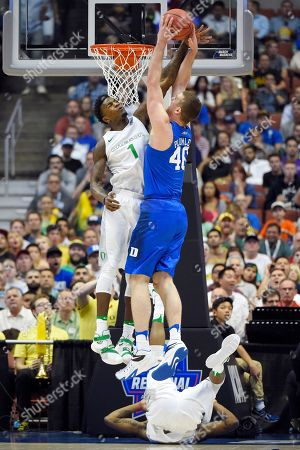Oregon forward Jordan Bell, left, blocks a shot of Duke center Marshall Plumlee during the first half of an NCAA college basketball game in the regional semifinals of the NCAA Tournament, in Anaheim, Calif