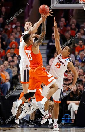 Mike Tobey, Michael Gbinije, Malcolm Brogdon Virginia's Mike Tobey (10) blocks a shot by Syracuse's Michael Gbinije (0) as Gbinije shoots over Virginia's Malcolm Brogdon (15) during the first half of a college basketball game in the regional finals of the NCAA Tournament, in Chicago
