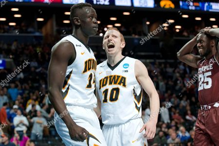 Stock Image of Quenton DeCosey, Peter Jok, Mike Gesell Temple guard Quenton DeCosey (25) reacts as Iowa guard Peter Jok, left, and guard Mike Gesell (10) celebrate after Jok scored a goal during overtime of a first round men's college basketball game in the NCAA Tournament, in New York. Iowa won 72-70 in overtime