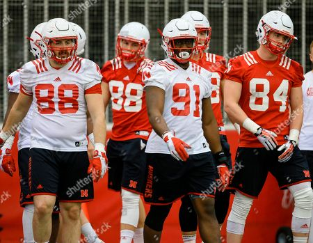 Ross Dzuris, Tyler Hoppes, Freedom Akinmoladun, Sam Cotton Nebraska defensive end Ross Dzuris, left, tight end Tyler Hoppes, second left, defensive end Freedom Akinmoladun (91) and tight end Sam Cotton (84) prepare to warm up at the start of NCAA college football spring practice in Lincoln, Neb