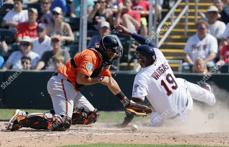 Francisco Pena, Kennys Vargas Baltimore Orioles catcher Francisco Pena (27) is unable to hold on to the ball as Minnesota Twins' Kennys Vargas (19) scores on a single by James Beresford in the sixth inning of a spring training baseball game, in Fort Myers, Fla. The Twins won 14-5