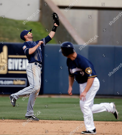 San Diego Padres' Nick Noonan catches a ball hit by Milwaukee Brewers' Rymer Liriano as Aaron Hill (9) watches during the fourth inning of a spring training baseball game, in Phoenix