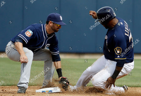 San Diego Padres' Nick Noonan tags out Milwaukee Brewers' Damien Magnifico as he is caught stealing second during the second inning of a spring training baseball game, in Phoenix