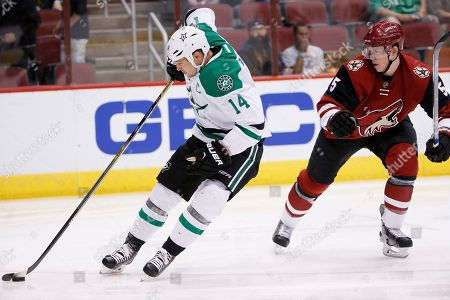 Jamie Benn, Connor Murphy Dallas Stars' Jamie Benn (14) controls the puck in front of Arizona Coyotes' Connor Murphy (5) during the first period of an NHL hockey game, in Glendale, Ariz. The Coyotes defeated the Stars 3-1