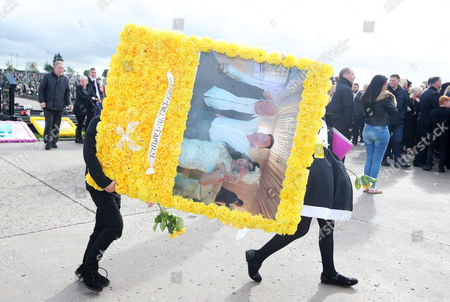 Wreaths are carried the graveside by young mourners.