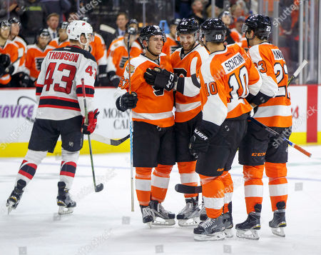 Stock Image of Travis Konecny, Andrew MacDonald, Brayden Schenn, Brandon Manning, Ben Thomson Philadelphia Flyers' Travis Konecny, center left, celebrates his deflected goal with teammates as New Jersey Devils' Ben Thomson, left, skates back to his bench during the second period of a preseason NHL hockey game, in Allentown, Pa