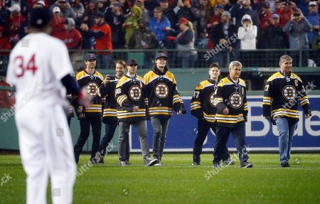 David Ortiz, Bobby Orr, Ray Bourque Former Boston Bruins' Ray Bourque, right, and Bobby Orr, second from right, lead members of the current team onto the field during ceremonies to honor Boston Red Sox's David Ortiz (34) before a baseball game against the Toronto Blue Jays in Boston