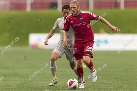 Ottawa Fury FC Lance Rozeboom (25) runs with the ball while Puerto Rico FC Paulo Ferreira Mendes (11) chases during the match between Puerto Rico FC and Ottawa Fury FC at TD Place in Ottawa, ON, Canada. Puerto Rico FC won the match by a score of 2-1