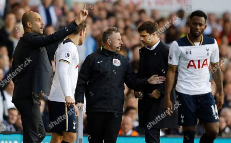 Tottenham Hotspur's manager Mauricio Pochettino, second right, is stopped by the 4th official J Moss, centre, as Manchester City's manager Pep Guardiola, left gestures to his players during the Premier League soccer match between Tottenham Hotspur and Manchester City at White Hart Lane stadium in London, . Spurs won the match 2-0