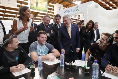 International Olympic Committee (IOC) president Thomas Bach (C) speaks with French athletes under the look of French basketball player Emmeline Ndongue (L) at the French national Institute of Sport and Physical Education (INSEP)