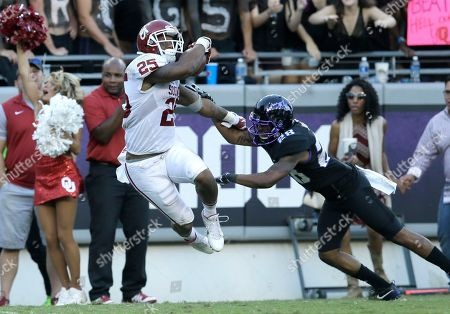 Joe Mixon, Tony James Oklahoma running back Joe Mixon (25) jumps for extra yards against TCU cornerback Tony James (28) during the second half of an NCAA college football game, in Fort Worth, Texas. Oklahoma won 52-46