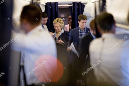 Hillary Clinton, Brian Fallon, Nick Merrill Democratic presidential candidate Hillary Clinton, second from left, Traveling Press Secretary Nick Merrill, right, speaks with National Press Secretary Brian Fallon, left, aboard her campaign plane in White Plains, N.Y., before traveling to Toledo, Ohio