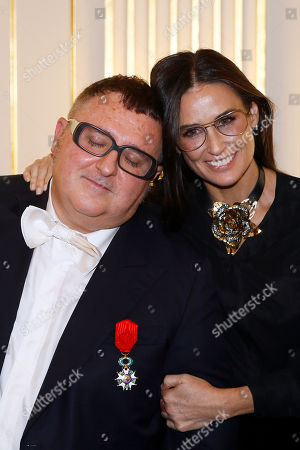Israeli American fashion designer Alber Elbaz, left, poses with actress Demi Moore after being awarded with the Officier de la Legion d'Honneur (Officer of the Legion of Honor) medal during a ceremony at the Culture Ministry in Paris