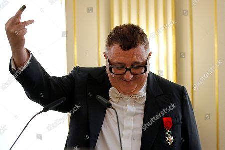 Israeli-Moroccan fashion designer Alber Elbaz shows a thimble that once belonged to a Holocaust survivor and was given to him by the woman's daughter as he delivers his speech, after being awarded with the Officier de la Legion d'Honneur (Officer of the Legion of Honor) medal at the Culture Ministry in Paris, . Elbaz said that he always keeps the thimble with him