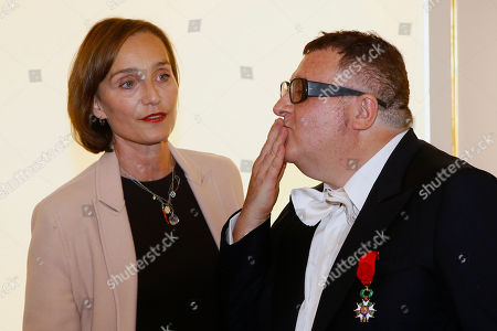 Israeli American fashion designer Alber Elbaz, right, flanked with British actress Kristin Scott Thomas, left, blows a kiss to the audience after being awarded with the Officier de la Legion d'Honneur (Officer of the Legion of Honor) medal during a ceremony at the Culture Ministry in Paris