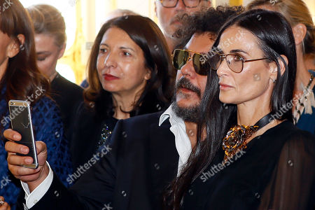 Actress Demi Moore, right, listens to the speech of Israeli American fashion designer Alber Elbaz after being awarded with the Officier de la Legion d'Honneur (Officer of the Legion of Honor) medal during a ceremony at the Culture Ministry in Paris