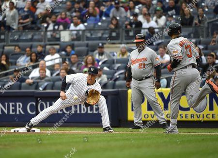 Wayne Kirby, Mark Teixeira, Manny Machado Baltimore Orioles first base coach Wayne Kirby (21) watches New York Yankees first baseman Mark Teixeira force out Manny Machado (13) at first base in the first inning of a baseball game, in New York