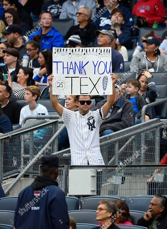 A New York Yankees fan holds up a poster for Mark Teixeira during the baseball game against the Baltimore Orioles, in New York. Teixeira is retiring after the game