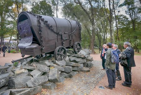 Visitors look at a monument to Gipsies killed in Babi Yar ravine where Nazi troops machine-gunned tens of thousands of Jews and others during WWII, in Kiev, Ukraine, . Ukraine marked the 75th anniversary of the 1941 Babi Yar massacre