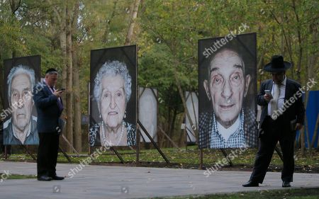 Jews pray reading sacred texts through cell phones standing near portraits of victims of Nazi concentration camps throughout Europe installed in Babi Yar ravine where Nazi troops machine-gunned tens of thousands of Jews during WWII, in Kiev, Ukraine, . Ukraine marked the 75th anniversary of the 1941 Babi Yar massacre
