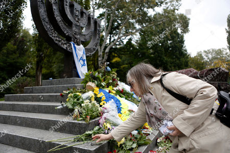 A woman lays a stone to Menorah monument in Babi Yar ravine where Nazi troops machine-gunned tens of thousands of Jews during WWII, in Kiev, Ukraine, . Ukraine marked the 75th anniversary of the 1941 Babi Yar massacre