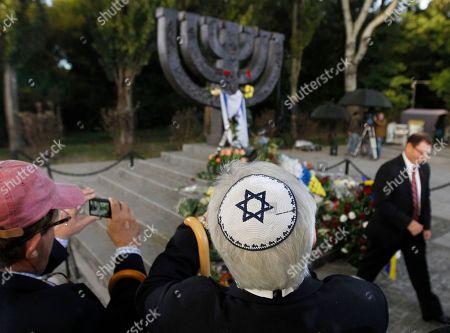 Men stand near the Menorah monument in Babi Yar ravine where Nazi troops machine-gunned tens of thousands of Jews during WWII, in Kiev, Ukraine, . Ukraine marked the 75th anniversary of the 1941 Babi Yar massacre