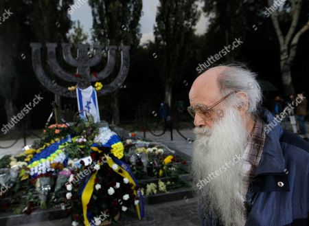 A man stands near the Menorah monument in Babi Yar ravine where Nazi troops machine-gunned tens of thousands of Jews during WWII, in Kiev, Ukraine, . Ukraine marked the 75th anniversary of the 1941 Babi Yar massacre