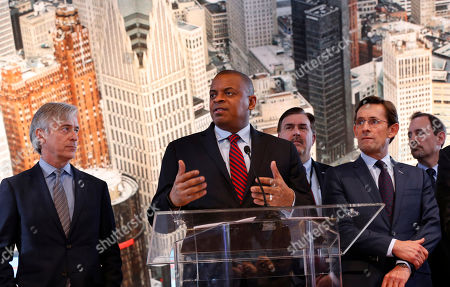 U.S. Transportation Secretary Anthony Foxx, second from left, speaks as auto executives listen at the North American International Auto Show in Detroit. Foxx announced Friday, Jan. 15, 2016, that the government and the auto industry have struck a peace treaty of sorts by agreeing to cooperate on safety issues in the future
