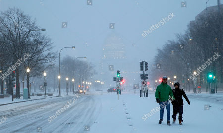 Madison Riley, left, and Katie Lantuh walk down the middle of Pennsylvania Avenue with the U.S. Capitol behind them, as the snow falls, in Washington. One in seven Americans will get at least half a foot of snow outside their homes when this weekend's big storm has finished delivering blizzards, gale-force winds, whiteout conditions and flooding to much of the eastern United States