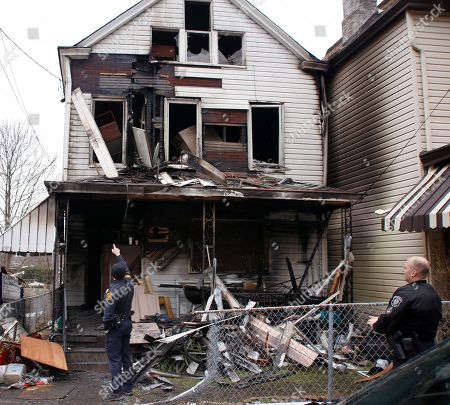 Pittsburgh police look over the front of a boarding house after a fatal fire, in Pittsburgh. Fire Chief Darryl Jones said heavy flames were visible when crews arrived, and the fire was so intense that it set off an alarm next door