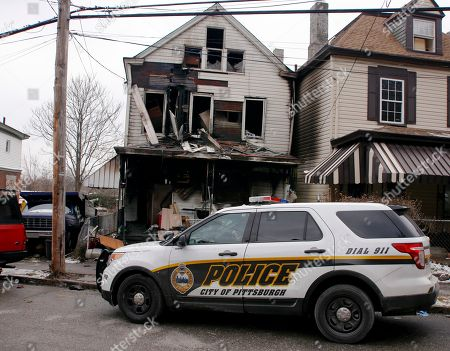 A Pittsburgh police vehicle sits parked in front of a boarding house after a fatal fire, in Pittsburgh. Fire Chief Darryl Jones said heavy flames were visible when crews arrived, and the fire was so intense that it set off an alarm next door