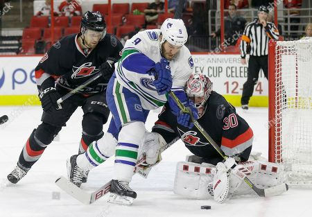 Stock Image of Cam Ward, Jay McClement, Brandon Prust Carolina Hurricanes goalie Cam Ward (30) and Jay McClement (18) defend the goal against Vancouver Canucks' Brandon Prust (9) during the first period of an NHL hockey game in Raleigh, N.C