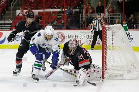Stock Photo of Cam Ward, Jay McClement, Brandon Prust Carolina Hurricanes goalie Cam Ward (30) and Jay McClement (18) defend the goal against Vancouver Canucks' Brandon Prust (9) during the first period of an NHL hockey game in Raleigh, N.C