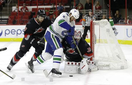 Cam Ward, Jay McClement, Brandon Prust Carolina Hurricanes goalie Cam Ward (30) and Jay McClement (18) defend the goal against Vancouver Canucks' Brandon Prust (9) during the first period of an NHL hockey game in Raleigh, N.C