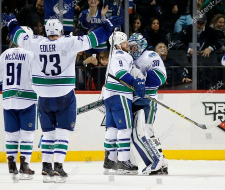 Brandon Prust, Ryan Miller, Alexander Edler, Jared McCann Vancouver Canucks right wing Brandon Prust (9) embraces Canucks goalie Ryan Miller (30) as Canucks defenseman Alexander Edler (23), of Sweden, celebrates after they defeated the New York Islanders 2-1 in a shootout in overtime of an NHL hockey game in New York, . Canucks center Jared McCann (91) looks on
