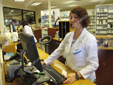 Pharmacist Sarah Burke checks a prescription at a Kroger pharmacy in Columbus, Ohio. Burke says a state database for pharmacists and other prescribers intended to help reduce Ohio's painkiller addiction epidemic is so easy to use she runs all prescriptions for controlled substances through it