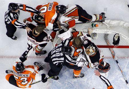 Referee Francis Charron (6) and linesman Scott Driscoll (68) try to break up a battle between Anaheim Ducks' Frederik Andersen (31), Ryan Kesler (17) and Jakob Silfverberg (33) and Philadelphia Flyers' Brayden Schenn (10), Jakub Voracek (93) and Shayne Gostisbehere (53) during the second period of an NHL hockey game, in Philadelphia