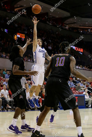 Stock Photo of Nic Moore, Clarence Williams, Kentrell Barkley SMU guard Nic Moore (11) shoots over East Carolina defenders Clarence Williams (10) and Kentrell Barkley during the first half of an NCAA college basketball game, in Dallas