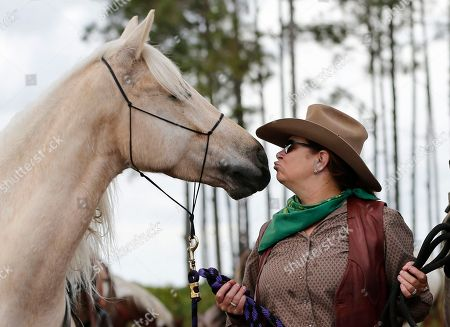 Wendy Wilson, Arcus Wendy Wilson of Ocala, Fla., kisses Arcus the horse as she and other riders stop for lunch and to water the horses during the Great Florida Cattle Drive 2016, in Kenansville, Fla