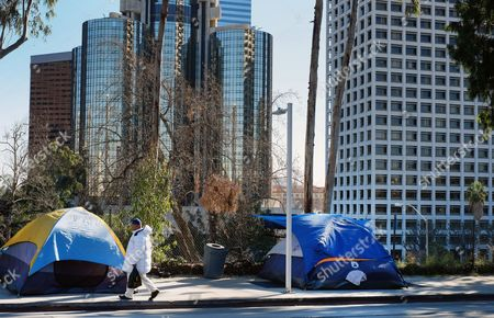 """Carl Thomas, 35, a homeless man walks up to his tent on the street in downtown Los Angeles, eats his lunch on . Some 7,000 volunteers will fan out as part of a three-night effort to count homeless people in most of Los Angeles County. Naomi Goldman, a spokeswoman of the organizer the Los Angeles Homeless Services Authority, said the goal is to """"paint a picture about the state of homelessness"""