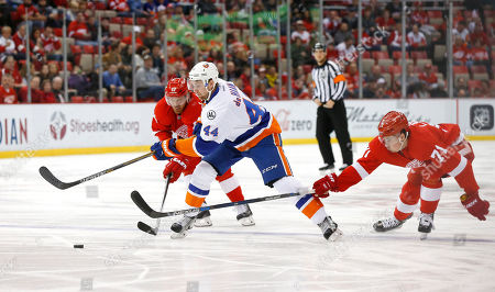 Detroit Red Wings center Brad Richards (17) and Dylan Larkin (71) defend New York Islanders defenseman Calvin de Haan (44) in the first period of an NHL hockey game in Detroit