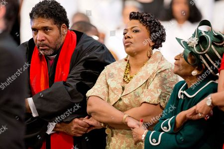 """William Barber, II, Bernice King, Christine King Farris Rev. Bernice King, center, and Christine King Farris, right, the daughter and sister of Rev Martin Luther King Jr., join hands along with Rev. Dr. William Barber, II, left, during the singing of """"We Shall Overcome"""" at the Rev. Martin Luther King Jr. holiday commemorative service at Ebenezer Baptist Church where King preached, in Atlanta"""