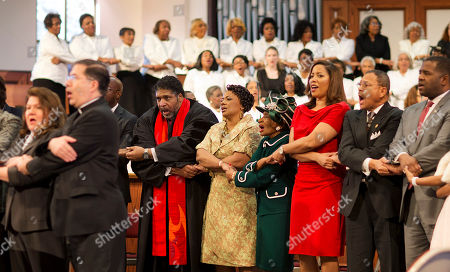 """Stock Photo of William Barber, II, Bernice King, Christine King Farris Rev. Bernice King, center, and Christine King Farris, right, the daughter and sister of Rev Martin Luther King Jr., join hands along with Rev. Dr. William Barber, II, left, during the singing of """"We Shall Overcome"""" at the Rev. Martin Luther King Jr. holiday commemorative service at Ebenezer Baptist Church where King preached, in Atlanta"""