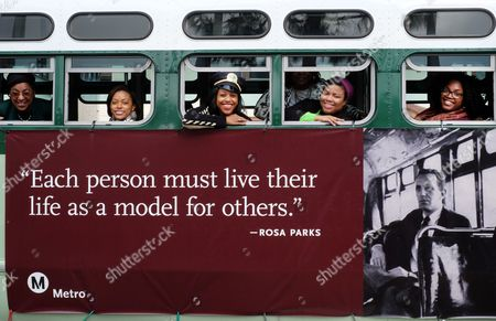 Kinya Claiborne, center, from the Los Angeles County Metropolitan Transportation Authority joins other Metro employees as they ride a replica of the bus that civil rights leader Rosa Parks rode in Montgomery, Ala., when she was arrested in 1955, as they participate in the 31st Annual Kingdom Day parade in Los Angeles on