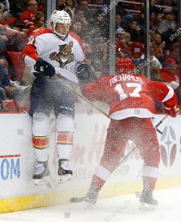 Detroit Red Wings center Brad Richards (17) checks Florida Panthers center Derek MacKenzie (17) into the boards in the second period of an NHL hockey game, in Detroit