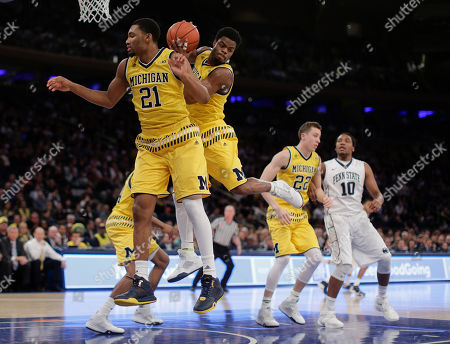 Michigan guard Derrick Walton Jr. grabs a rebound alongside guard Zak Irvin (21) during the first half of an NCAA college basketball game against Penn State, at Madison Square Garden in New York