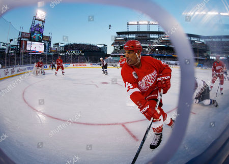Chris Chelios In this view through a fisheye lens, Detroit Red Wings defenseman Chris Chelios takes control of the puck against the Colorado Avalanche during the first period of the Stadium Series alumni game, at Coors Field in Denver on